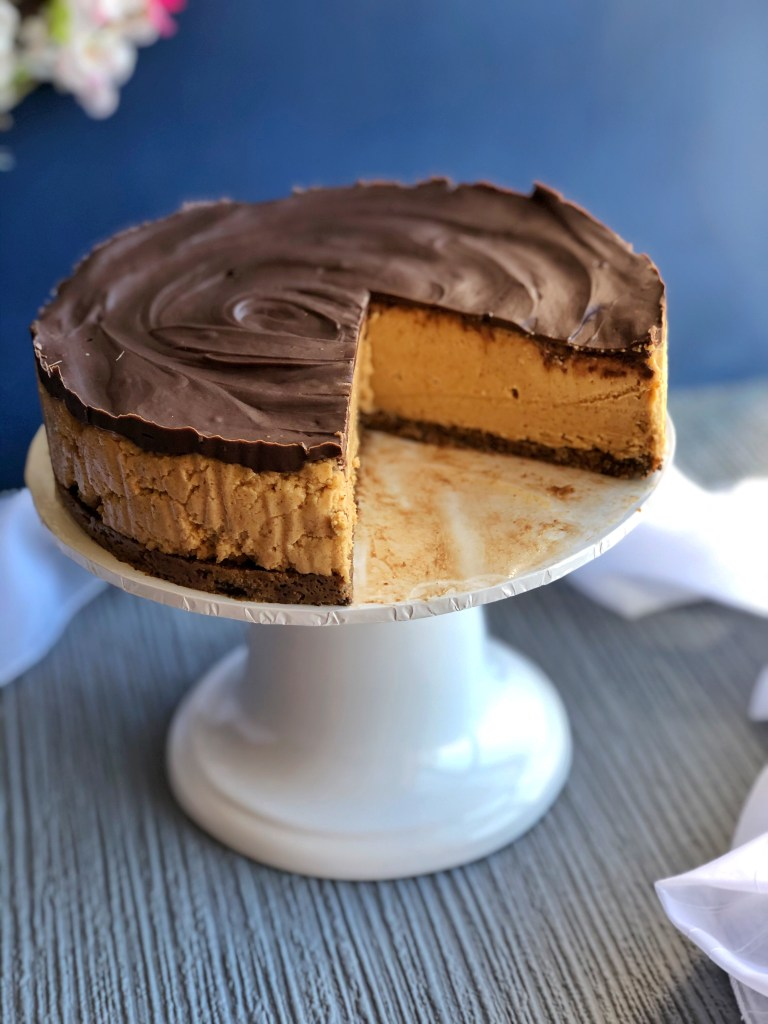 No bake chocolate peanut butter cheesecake on a stand.
