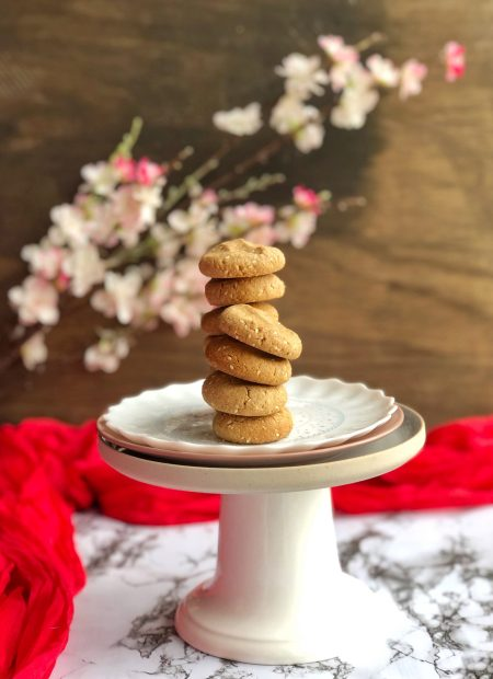 Stacking sesame almond butter cookies on a cake stand.