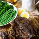 Shoulder of lamb with a jug of gravy and a bowl of green beans and tender stem broccoli