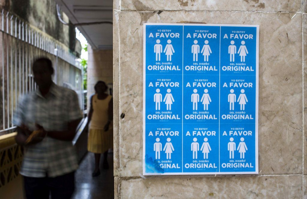"""Poster with symbols of heterosexual couples placed on the outside of a church of the Evangelical League with the slogan """"I am in favor of the original design,"""" against the legalization of same-sex marriages in Cuba. Photo: Desmond Boylan / AP."""