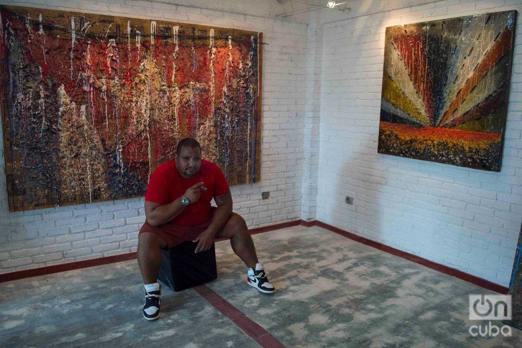 Cuban artist Michel Mirabal along with works of the personal exhibition he is exhibiting in his gallery workshop, as part of the collateral activities of the 13th Havana Biennial. Photo: Otmaro Rodríguez.