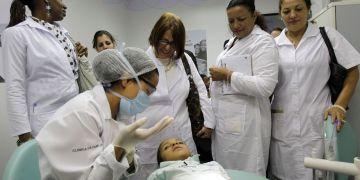 Cuban doctors observe a dental procedure during a training session at a health clinic in Brasilia. Photo: Eraldo Peres / AP.