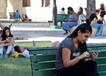 Several persons use their mobile phones in a park with Internet connection via public Wi-Fi, on December 27, 2018, in Havana. Photo: Ernesto Mastrascusa / EFE / Archive.