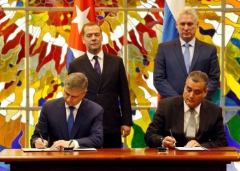 Cuban President Miguel Díaz-Canel Bermúdez (r-standing) and Russian Prime Minister Dmitry Medvedev (l-standing), observe the signing of a bilateral agreement between the two countries in Havana, on October 3, 2019. Photo: Ernesto Mastrascusa / POOL / EFE.