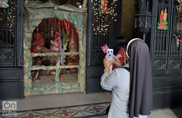 Una religiosa toma foto en la Iglesia de Reina. Foto: Otmaro Rodríguez Díaz.