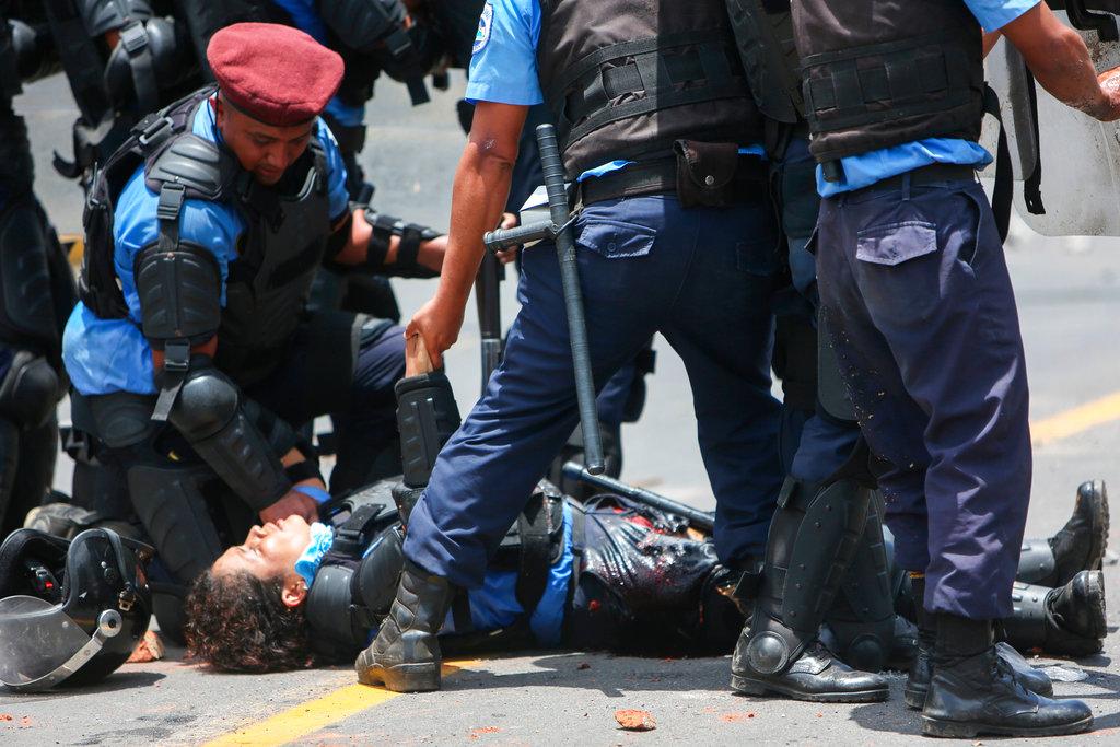 En esta imagen, tomada el 20 de abril de 2018, policías antimotines atienden a una compañera herida en una pierna por un mortero de fabricación casera lanzado por los manifestantes en Managua, Nicaragua. Los choques, que enfrentan a contrarios a la reforma de la seguridad social contra policías antimotines y grupos progubernamentales, sacudieron la capital y media docena de ciudades más y causaron 63 muertos, según un grupo de derechos no gubernamental. Foto: Alfredo Zuniga/AP.