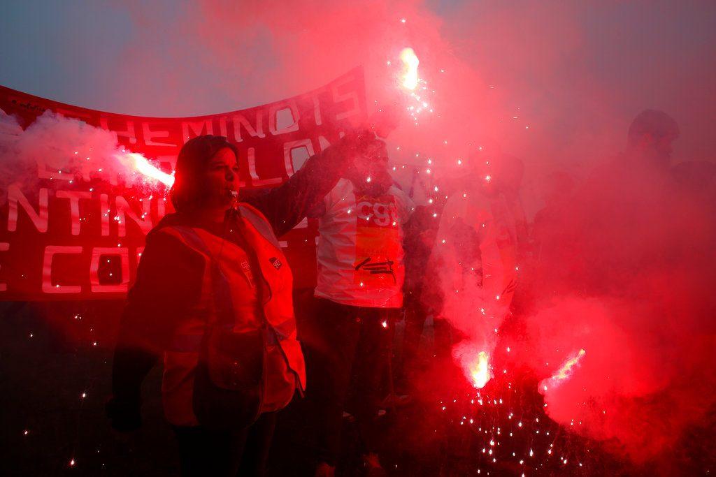 Empleados ferroviarios encienden bengalas durante una protesta en París, el 9 de abril. Foto: Thibault Camus / AP.
