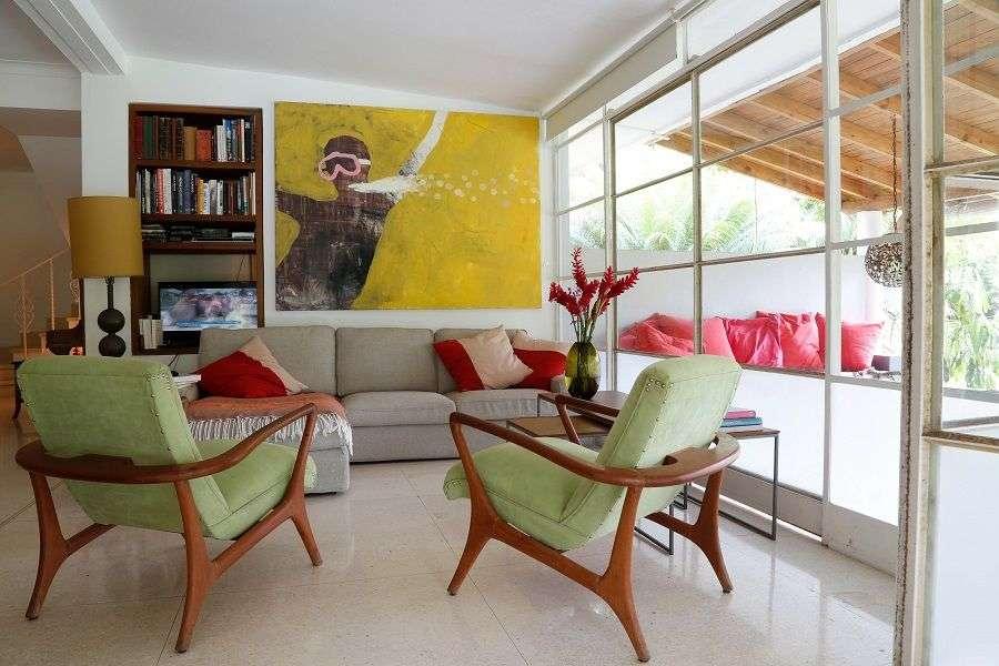 En la sala de estar íntimamente escalonada de Katharina Voss y Enrique Arias, sillones cubanos de mediados del siglo XX enmarcan una pintura de Alejandro Campins. Foto: Carlos Otero.