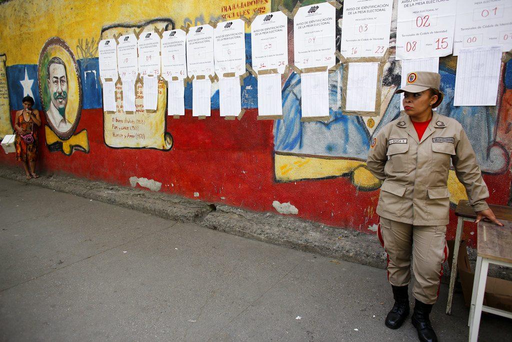 Miembro de la milicia bolivariana se detiene frente a las listas de votantes en un centro electoral durante los comicios presidenciales en Caracas, Venezuela, el domingo 20 de mayo de 2018. Foto: Ariana Cubillos / AP