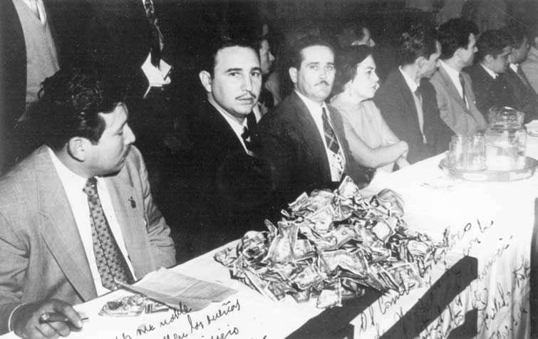 Durante el acto en el Palm Garden Hotel, aparece junto al también revolucionario Juan Manuel Márquez. La colecta de dinero donado por cubanos emigrados es uno de los objetivos del viaje.