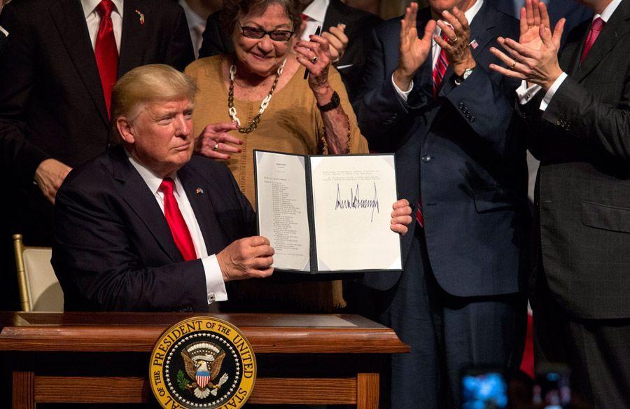 Donald Trump muestra el memorando presidencial sobre la política con Cuba al finalizar su discurso en el teatro Manuel Artime de la Pequeña Habana, en Miami, el 16 de junio de 2017. Foto: Cristobal Herrera / EFE.