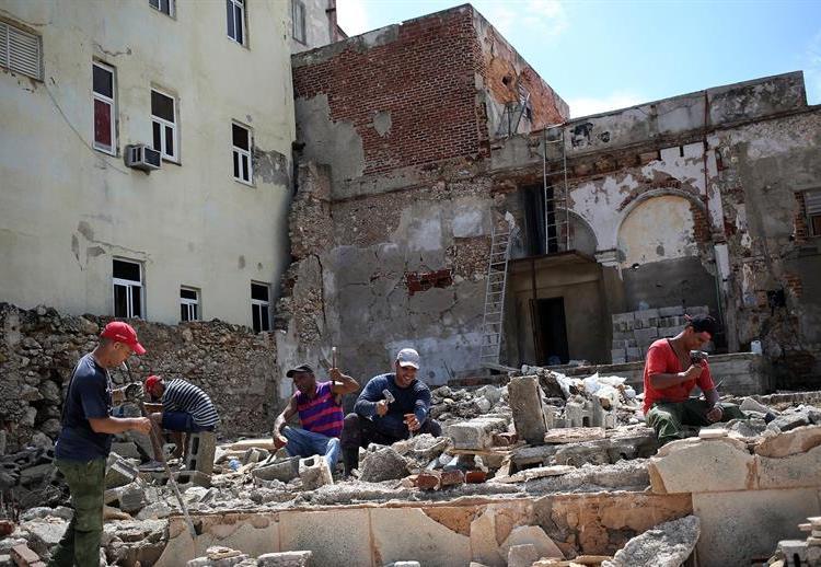 Obreros y militares trabajan en la rehabilitación de las zonas afectadas por Irma, el miércoles 13 de septiembre, en La Habana. Unas 4.288 viviendas resultaron dañadas en capital cubana, donde ocurrieron 157 derrumbes totales y 986 parciales, según reportes oficiales preliminares. Foto: Alejandro Ernesto / EFE.