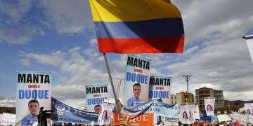 Un simpatizante del candidato presidencial Iván Duque ondea una bandera colombiana durante un evento de campaña en Soacha, a las afueras de Bogotá, el 12 de mayo de 2018. Foto: Fernando Vergara / AP.