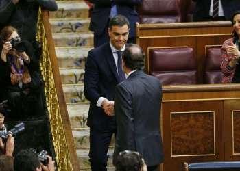 El presidente del gobierno español Mariano Rajoy, de espaldas, estrecha la mano del líder socialista Pedro Sánchez luego de una moción de desconfianza en el paramento en Madrid el viernes, 1ro de junio de 2018. Sánchez fue juramentado el sábado como nuevo jefe del gobierno. Foto: Francisco Seco / AP.