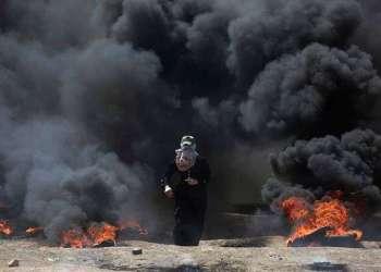 Una mujer palestina atraviesa una densa nube de humo negro provocada por la quema de neumáticos durante las protestas en la frontera entre la Franja de Gaza e Israel. Foto: Khalil Hamra / AP.