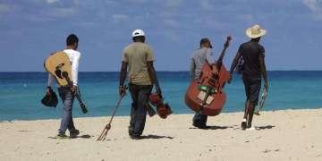 Grupo de soneros camina por playa turística en Cuba. Foto: www.pxhere.com