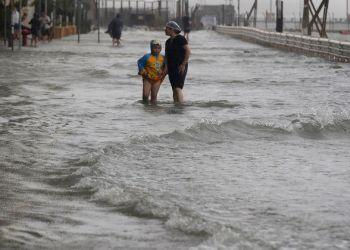 Unas personas caminan a través de una inundación causada por el tifón Mangkhut en Hong Kong, el domingo 16 de septiembre de 2018. Foto: Vincent Yu/AP.