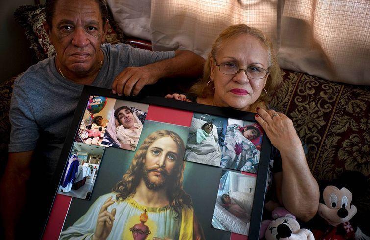 Juan Manuel González (izq) y María González Muñoz posan el 4 de septiembre en San Juan con un retrato de Jesús y fotos de su hermana Ramona, una mujer incapacitada que falleció a los 59 años de una septicemia. Los hermanos dicen que murió a raíz de una úlcera que no fue debitamente tratada después del paso del huracán María por Puerto Rico. Foto: Ramón Espinosa / AP.