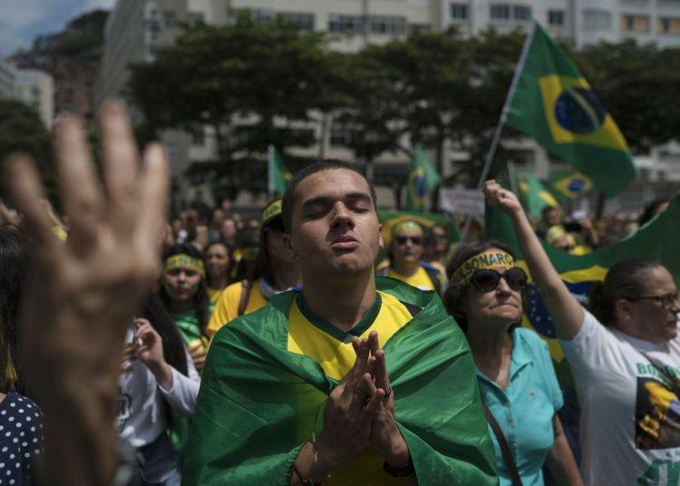 Una multitud escucha el himno nacional en el acto de campaña del candidato presidencial ultraderechista Jair Bolsonaro en Río de Janeiro, el domingo 21 de octubre de 2018. Foto: Leo Correa / AP.