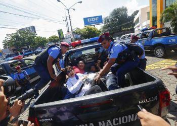 Manifestantes son detenidos y transportados por policías después de disolver una marcha en Managua, Nicaragua, el domingo 14 de octubre de 2018. (AP Foto/Alfredo Zúñiga)