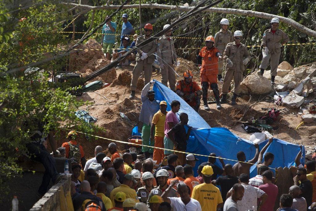 Vecinos, voluntarios y bomberos realizan tareas de búsqueda y rescate tras un deslizamiento en el morro Boa Esperança en Niteroi, Brasil, 10 de noviembre de 2018. Catorce muertos y 11 heridos es el resultado del deslizamiento, aunque las autoridades dijeron que podría haber más víctimas el domingo 11 de noviembre de 2018. (AP Foto/Leo Correa)