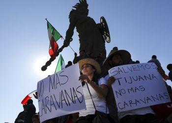 Manifestantes sostienen carteles bajo la estatua del emperador azteca Cuauhtémoc como protesta contra los miles de migrantes centroamericanos que han llegado a la ciudad en Tijuana, México, el domingo 18 de noviembre de 2018. Foto: Rodrigo Abd / AP.