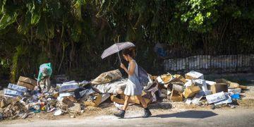 Una mujer camina junto a un montón de basura en el barrio Vedado de La Habana, Cuba. Foto: Desmond Boylan / AP / Archivo.
