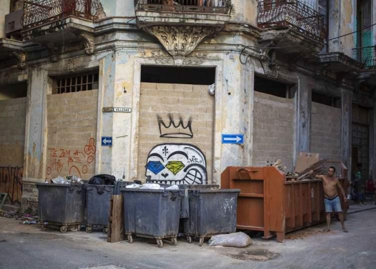 En esta foto del 22 de octubre de 2018, un hombre arroja basura en un contenedor en La Habana Vieja, Cuba.  (AP Foto AP / Desmond Boylan)
