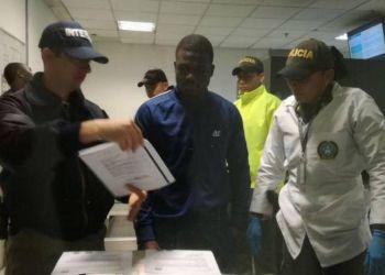 El colombiano Fredis Valencia (centro), implicado en el asesinato de dos migrantes cubanos en 2016, junto a oficiales de la policía colombiana antes de su extradición a EE.UU. Foto: zonacero.com