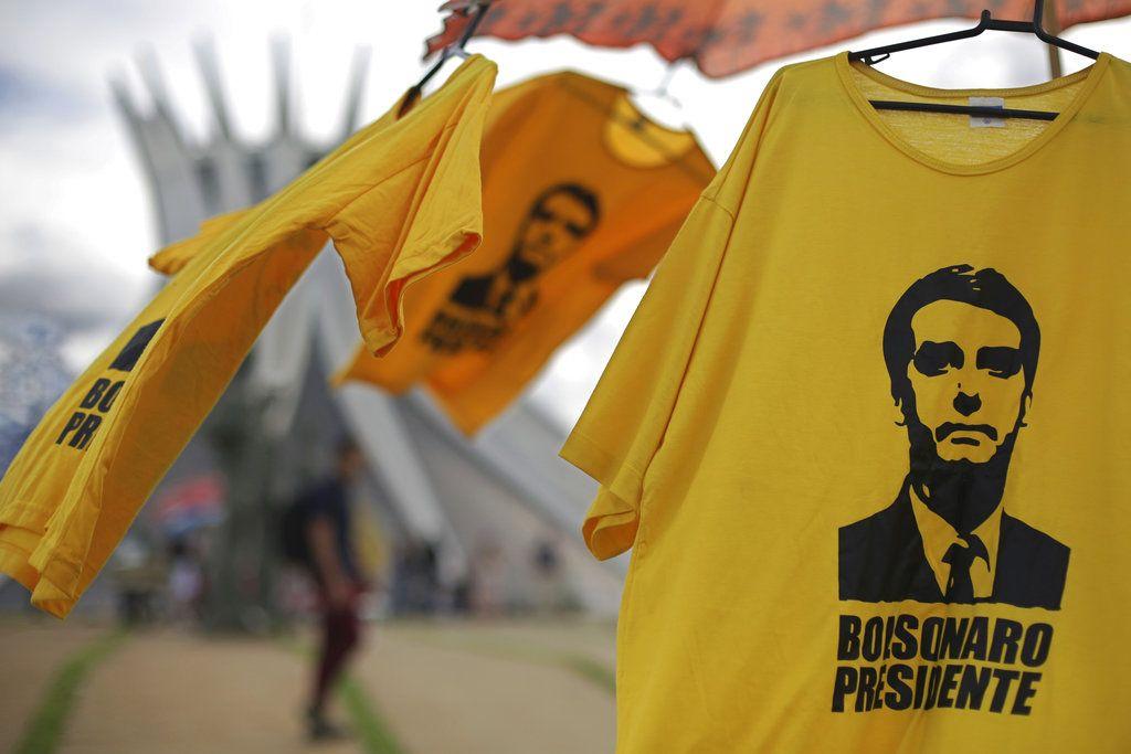 Camisetas con la imagen del presidente electo de Brasil, Jair Bolsonaro, se exhiben para la venta frente a la Catedral de Brasilia, el viernes 28 de diciembre de 2018. (AP Foto/Eraldo Peres)