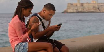 Una pareja de jóvenes se conecta a internet desde el malecón, el 27 de diciembre de 2018, en La Habana. Foto: Yander Zamora / EFE.