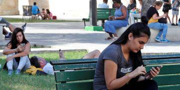 Varias personas usan sus teléfonos móviles en un parque con conexión a Internet mediante wifi pública, el 27 de diciembre de 2018, en La Habana. Foto: Ernesto Mastrascusa / EFE / Archivo.