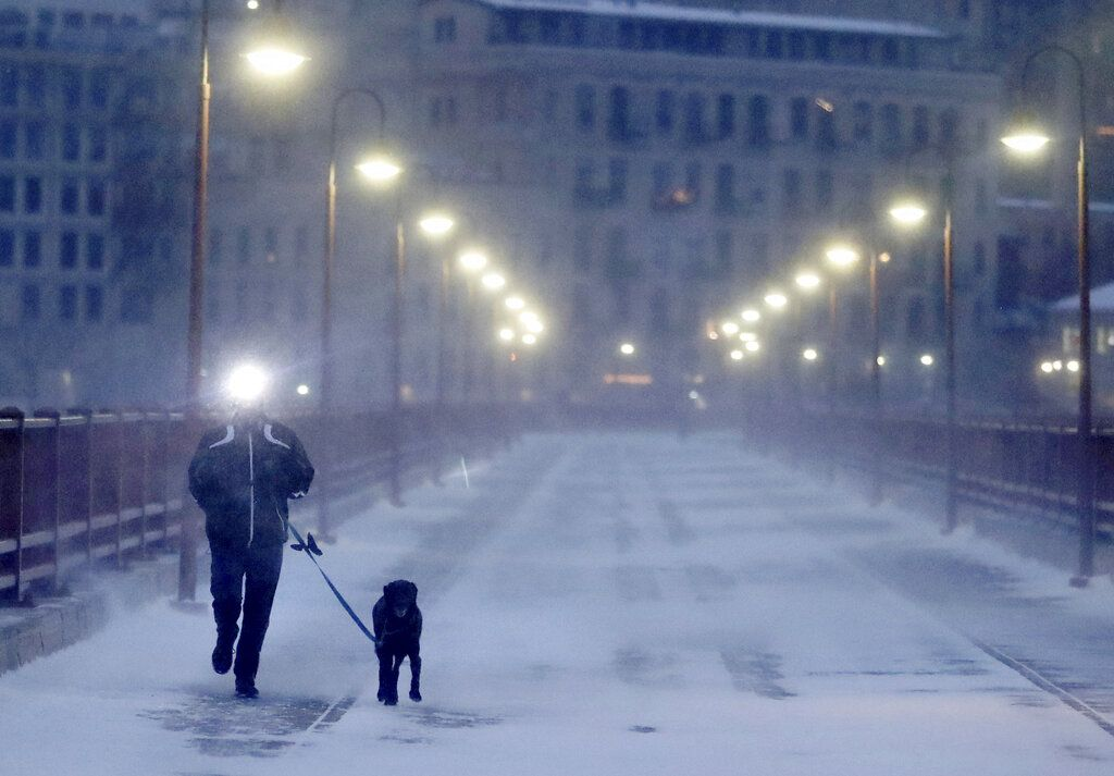 Un corredor y su perro soportan el frío extremo mientras cruzan el puente Stone Arch el jueves 24 de enero de 2019. (David Joles/Star Tribune vía AP)
