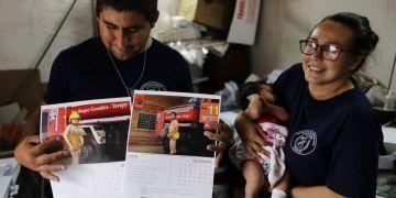 La bombera Fátima Olmedo (derecha) sostiene a su hija de dos meses Samara mientras su esposo, Rodrigo Giménez, muestra las páginas del calendario donde salen desnudos, en Asunción, Paraguay. Foto: Jorge Saenz / AP.