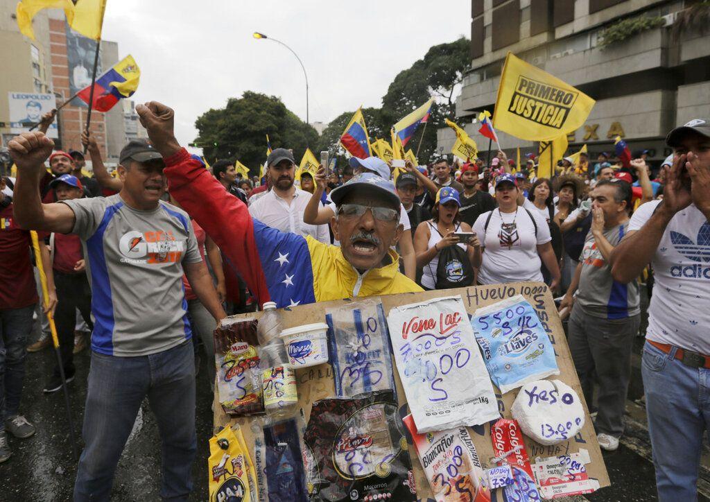 Un opositor sostiene un cartón con bolsas de productos básicos y sus precios durante una protesta contra el presidente venezolano Nicolás Maduero en Caracas, el miércoles 23 de enero de 2019. (AP Foto/Fernando Llano)