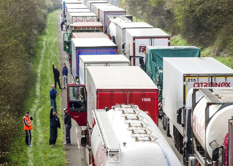 Conductores de camión esperan junto a sus vehículos en una autopista entre Bruselas y Luxemburgo, en Spontin, Bélgica, 6 de abril de 2016. Foto: Geert Vanden Wijngaert / AP.