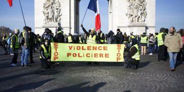 """Manifestantes de los chalecos amarillos se reúnen en el Arco del Triunfo con una pancarta que dice """"Paren la violencia policial"""" durante una movilización en París, el sábado 16 de febrero de 2019. Foto: Thibault Camus / AP."""
