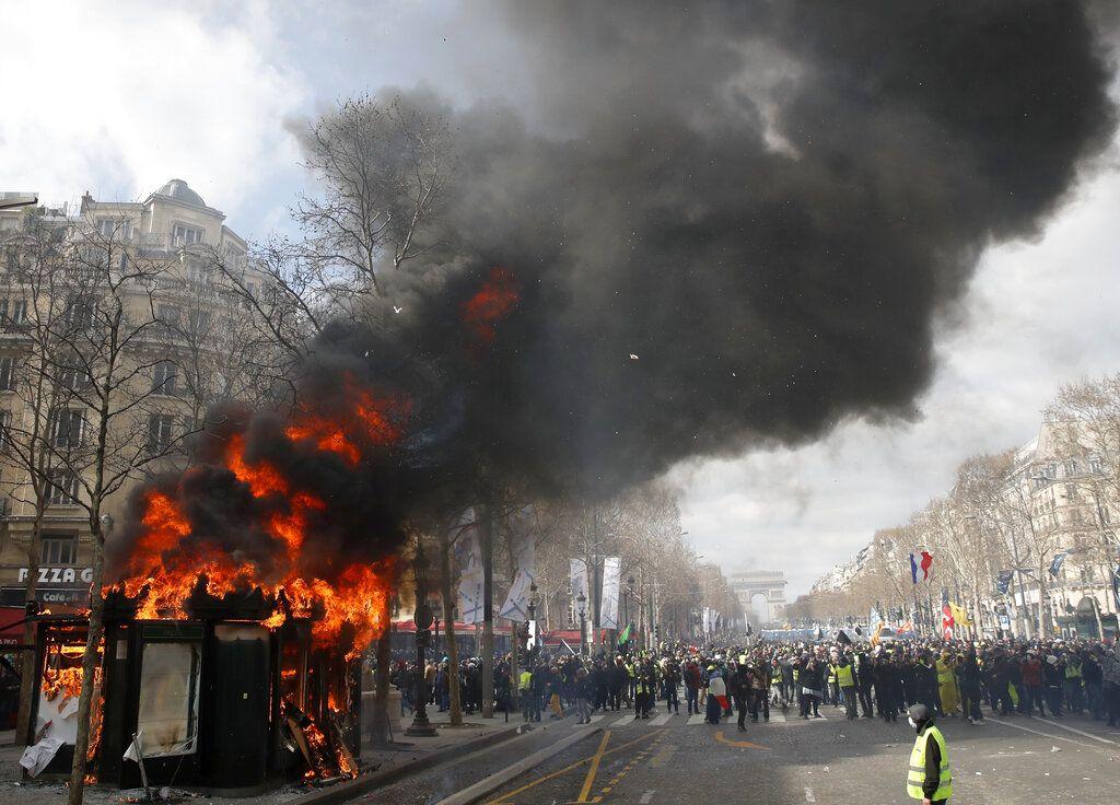 Un quiosco de periódicos envuelto en llamas durante una manifestación de los chalecos amarillos sobre la avenida de los Campos Elíseos, en París, el sábado 16 de marzo de 2019. Foto: Christophe Ena / AP.