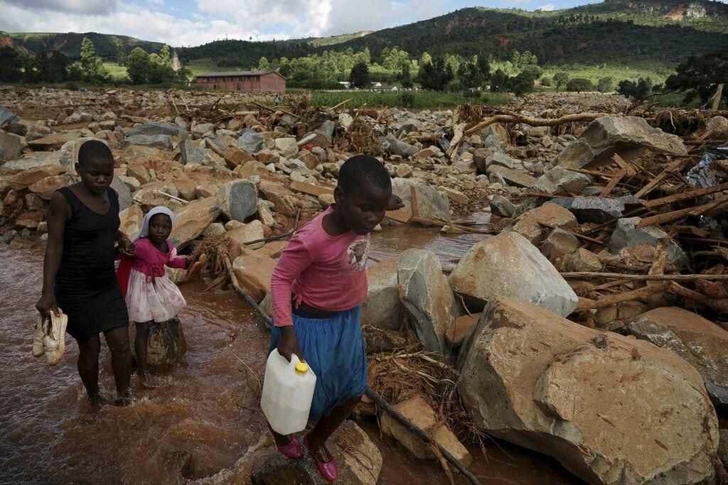 En imagen del viernes 22 de marzo de 2019, un grupo de menores cruza un riachuelo en Chimanimani, Zimbabue, en una zona devastada tras el paso de un ciclón en el sur de África. (AP Foto/KB Mpofu)