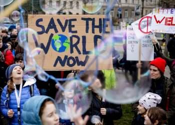 """Jóvenes se manifiestan a favor de la adopción de medidas contra el cambio climático con un letrero que dice: """"Salven al mundo ahora"""" durante una concentración en Berlín, Alemania, el viernes 22 de marzo de 2019. Foto: Christoph Soeder / dpa vía AP."""