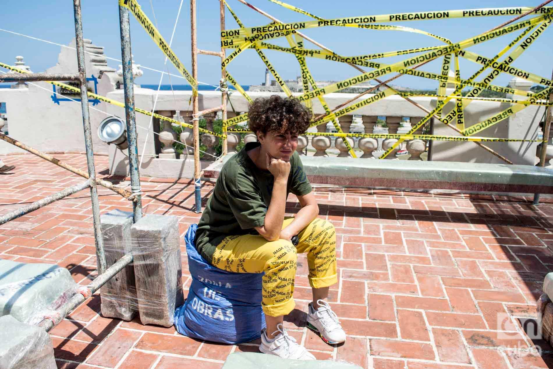 """La diseñadora cubana Idania del Río junto a la instalación artística """"País en construcción"""", del emprendimiento de diseño Clandestina, en la Embajada de España como parte de la XIII Bienal de La Habana. Foto: Otmaro Rodríguez."""