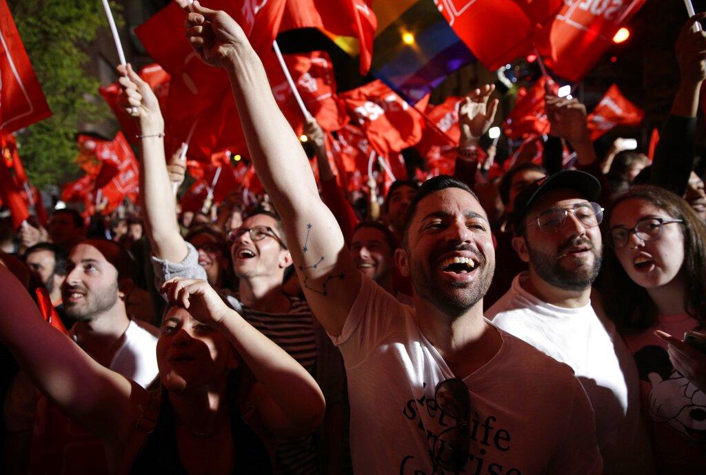 Partidarios de Pedro Sánchez, jefe del gobierno español y candidato del PSOE, festejan al enterarse de los resultados de los comicios en Madrid, el domingo 28 de abril de 2019. (AP Foto/Andrea Comas)