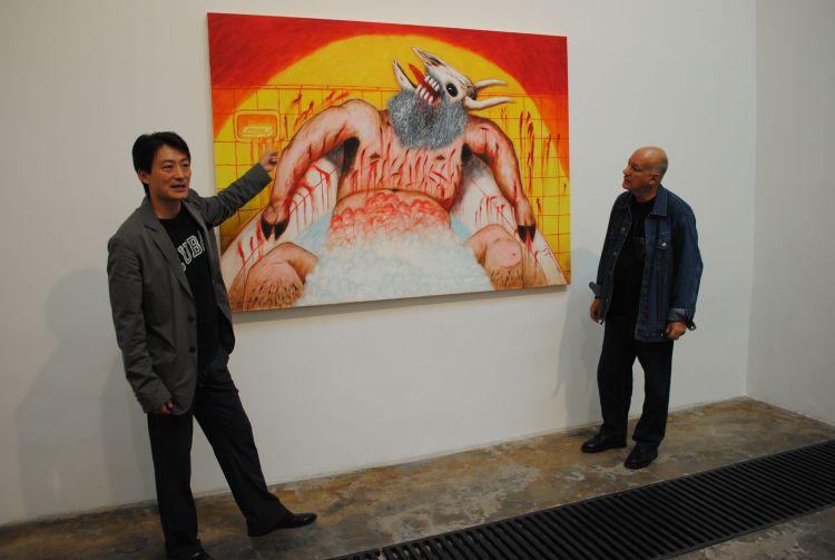 El galerista chino Cheng Xin Dong junto a la obra del artista cubano Rafael Zarza.