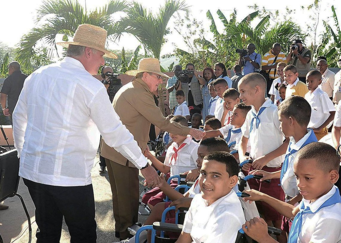 """El expresidente cubano Raúl Castro (c) y el actual mandatario, Miguel Díaz-Canel, saludan a estudiantes de la escuela """"Amistad Cuba-Vietnam"""" para niños con discapacidad, inaugurada el 23 de abril de 2019 en Santiago de Cuba. Foto: @aparedesrebelde / Twitter."""