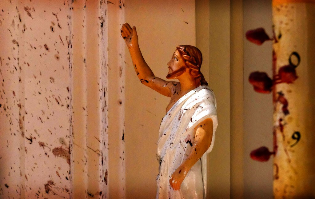 Manchas de sangre se en el muro y en una estatua de Jesucristo después de una explosión en la iglesia de San Sebastián, en Colombo, Sri Lanka, el domingo 21 de abril de 2019. Foto: AP.