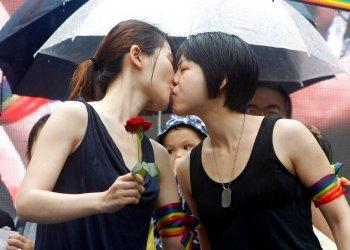 Dos muejres, activistas en favor del matrimonio homosexual, se besan en el exterior del parlamento de Taiwán, en Taipei, el 17 de mayo de 2019, tras la aprobación de una ley que legaliza las uniones entre personas del mismo sexo. (AP Foto/Chiang Ying-ying)