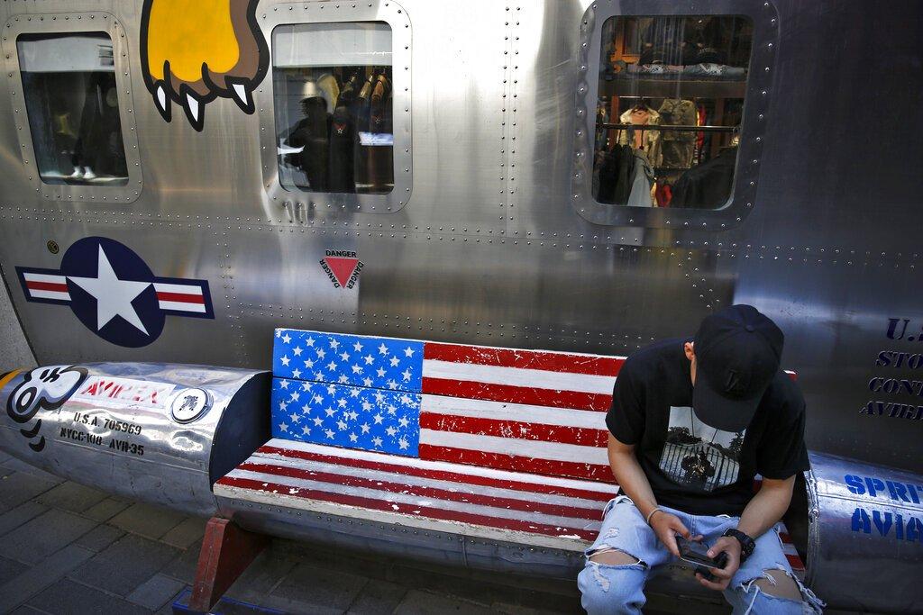 Un hombre navega en su smartphone en una banca decorada con la bandera estadounidense afuera de una tienda que vende marcas de Estados Unidos en un popular centro comercial en Beijing, el lunes 13 de mayo de 2019. (AP Foto/Andy Wong)