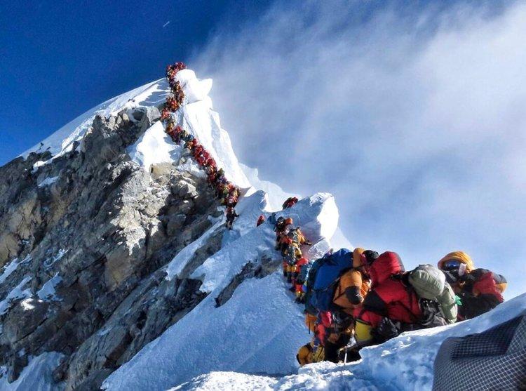 En esta fotografía del 22 de mayo de 2019, una larga fila de montañeros ascienden al pico del Everest. (Nimsdai Project Possible vía AP)