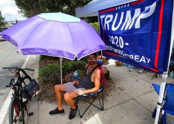 Ray Renaud, de Daytona Beach, Florida, se cubre con una sombrilla mientras simpatizantes del presidente Donald Trump acampan frente al Amway Center el lunes 17 de junio de 2019, antes de un evento para dar inicio a la campaña de reelección 2020 en Orlando, Florida. (Joe Burbank/Orlando Sentinel via AP)
