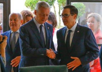 El ministro francés de Finanzas, Bruno Le Maire, a la izquierda, estrecha la mano con el secretario del Tesoro de Estados Unidos, Steve Mnuchin, junto al ministro alemán de Finanzas, Olaf Scholz, al fondo a la izquierda, durante una reunión de los responsables de finanzas del G7 en Chantilly, al norte de París, el jueves 18 de julio de 2019.  Foto: Michel Euler/ AP.